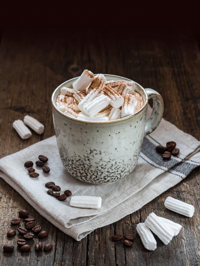 Taza de café grande con la leche y la melcocha asperjadas con canela en una tabla de madera imágenes de archivo libres de regalías