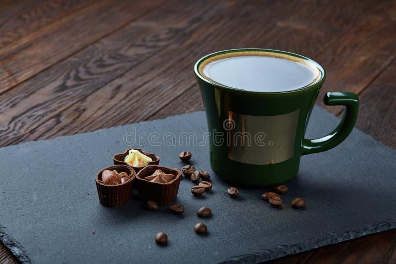 Taza de café, granos de café, caramelos de chocolate en el tablero de piedra sobre el fondo de madera, foco selectivo, primer imagen de archivo