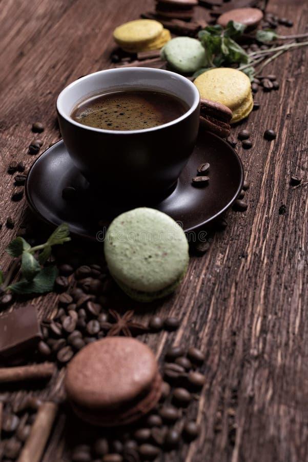 Taza de café, habas, chocolate y macarrones del color en la tabla foto de archivo libre de regalías