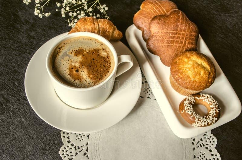 Taza de café instantáneo con el panecillo y las galletas en fondo negro imagen de archivo