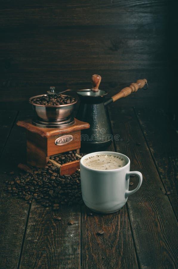 Taza de café, molino y jezve en la tabla rústica oscura fotografía de archivo libre de regalías