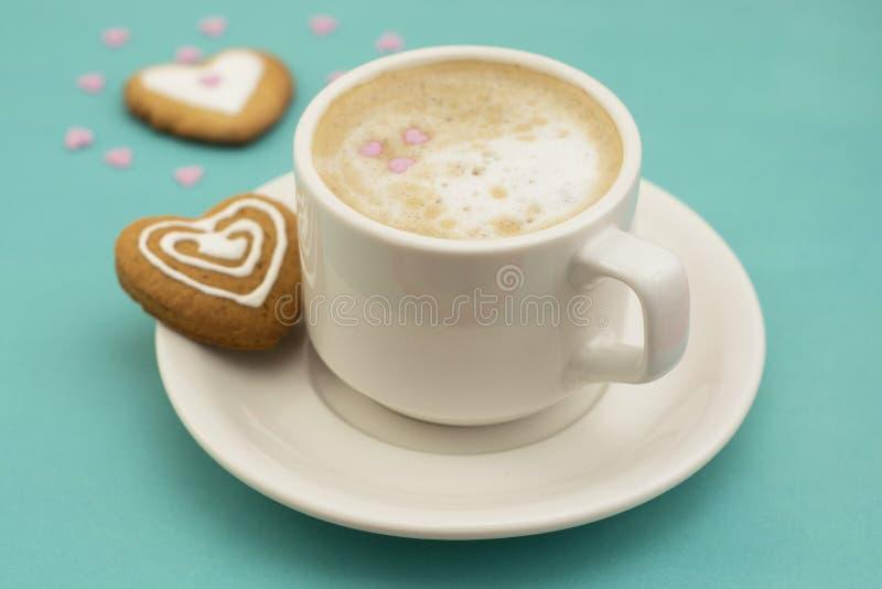 Taza de café o latte y galletas en forma de corazón, galletas Fondo azul, espacio de la copia Amantes de la bebida del cafeína Ca imagenes de archivo