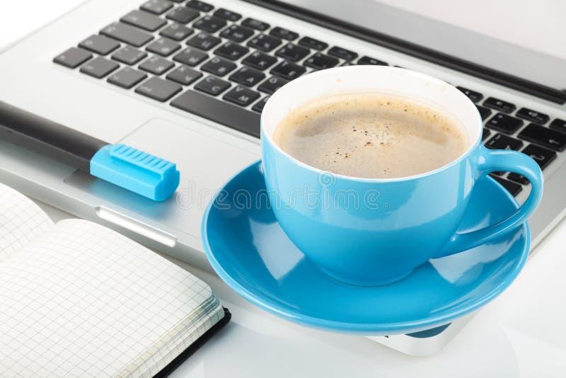 Taza de café, ordenador portátil y materiales de oficina azules imagen de archivo libre de regalías
