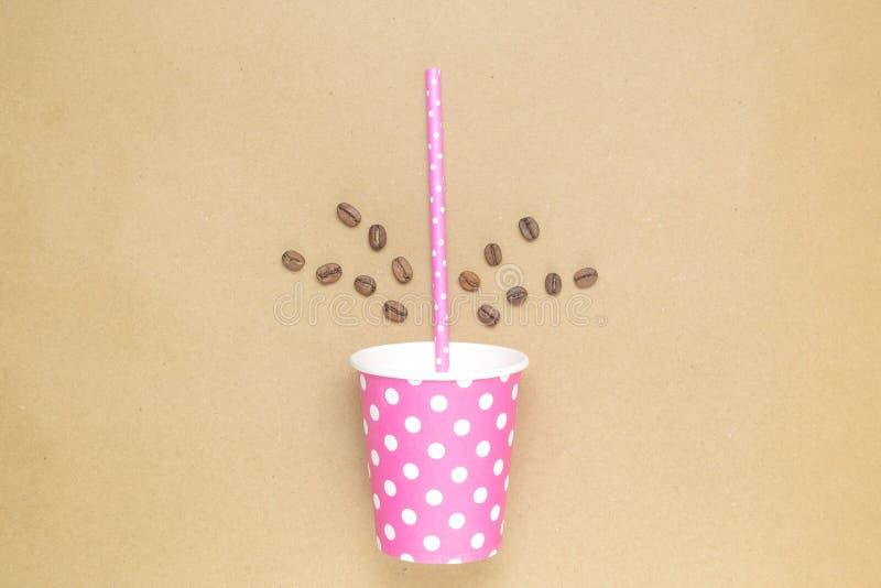 Taza de café de papel con la paja de beber y los granos de café fotografía de archivo libre de regalías