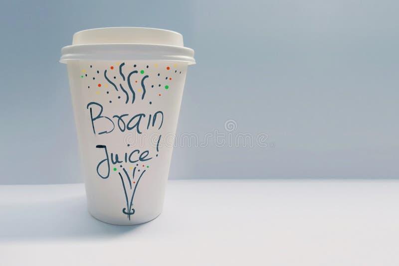 Taza de café de papel disponible blanca con las palabras Brain Juice Written en ella foto de archivo