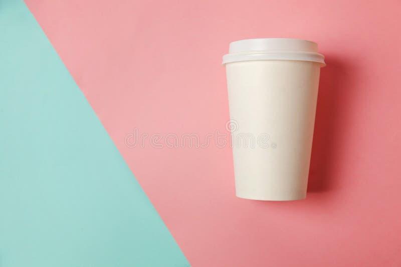 Taza de café de papel en fondo azul y rosado imágenes de archivo libres de regalías