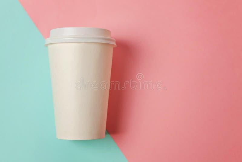 Taza de café de papel en fondo azul y rosado fotos de archivo