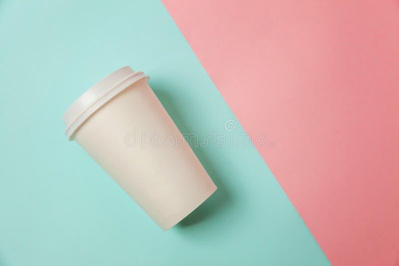 Taza de café de papel en fondo azul y rosado foto de archivo