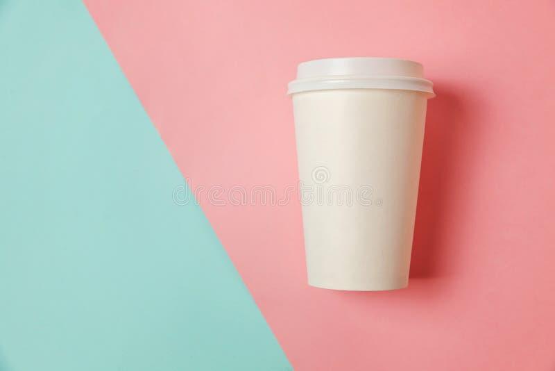 Taza de café de papel en fondo azul y rosado imagenes de archivo