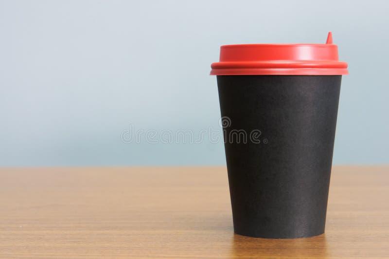 Taza de café de papel en negro con la tapa roja ilustración del vector