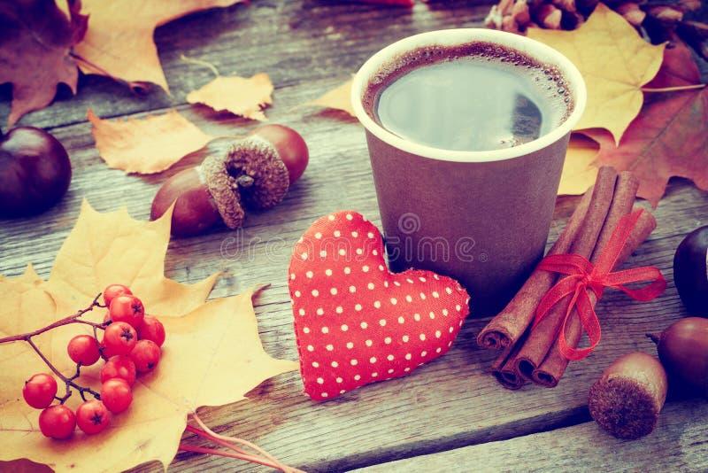 Taza de café que se calienta, corazón rojo y vida del otoño aún fotos de archivo libres de regalías