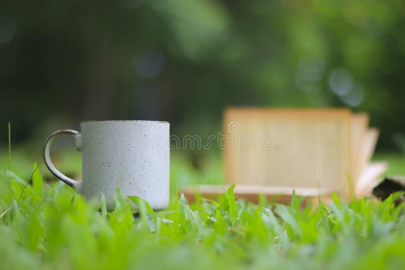 Taza de café retra con el libro en la hierba verde fotografía de archivo libre de regalías