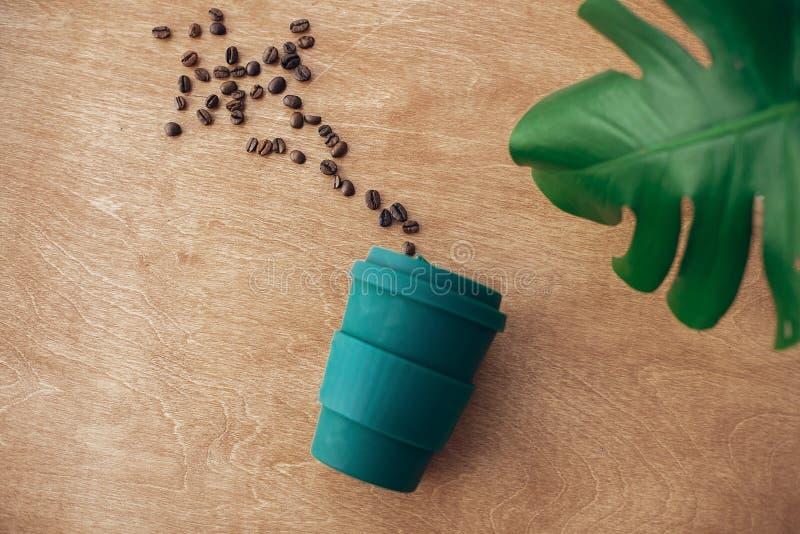 Taza de café reutilizable elegante del eco en fondo de madera con los granos de café asados y la hoja verde del monstera Plástico imagen de archivo