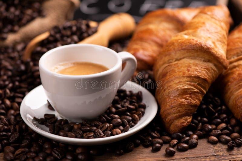 Taza de café rodeada por los granos de café fotografía de archivo
