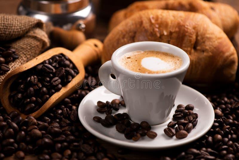 Taza de café rodeada por los granos de café fotografía de archivo libre de regalías