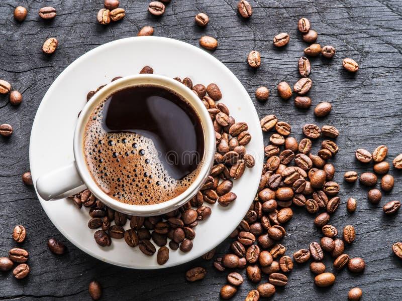 Taza de café rodeada por los granos de café Visión superior imagenes de archivo