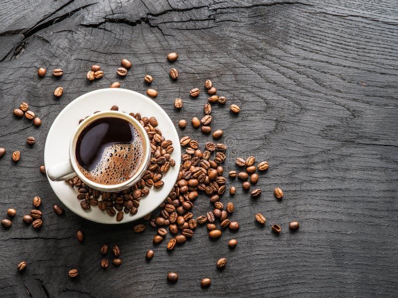 Taza de café rodeada por los granos de café Visión superior foto de archivo libre de regalías