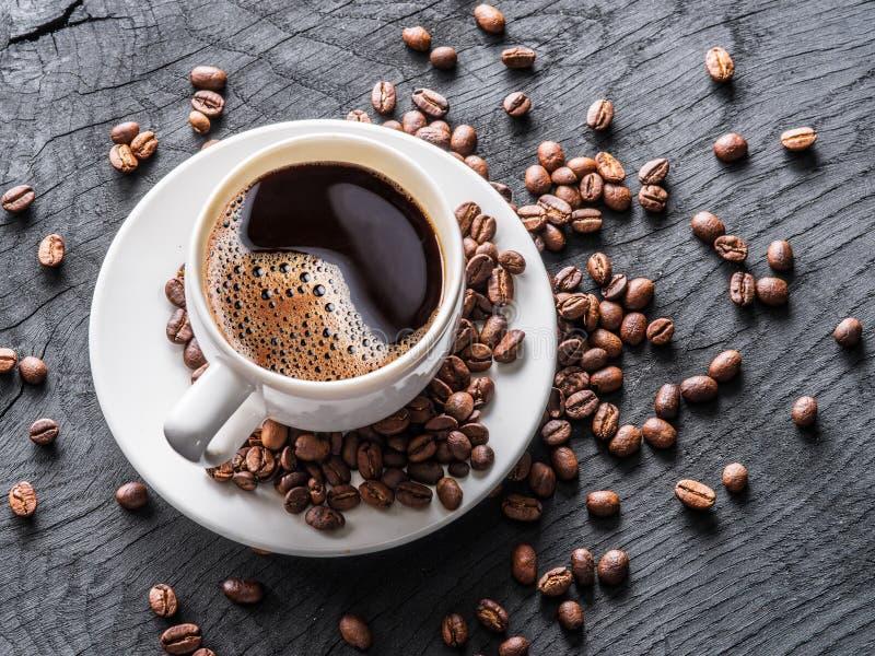 Taza de café rodeada por los granos de café Visión superior fotografía de archivo libre de regalías