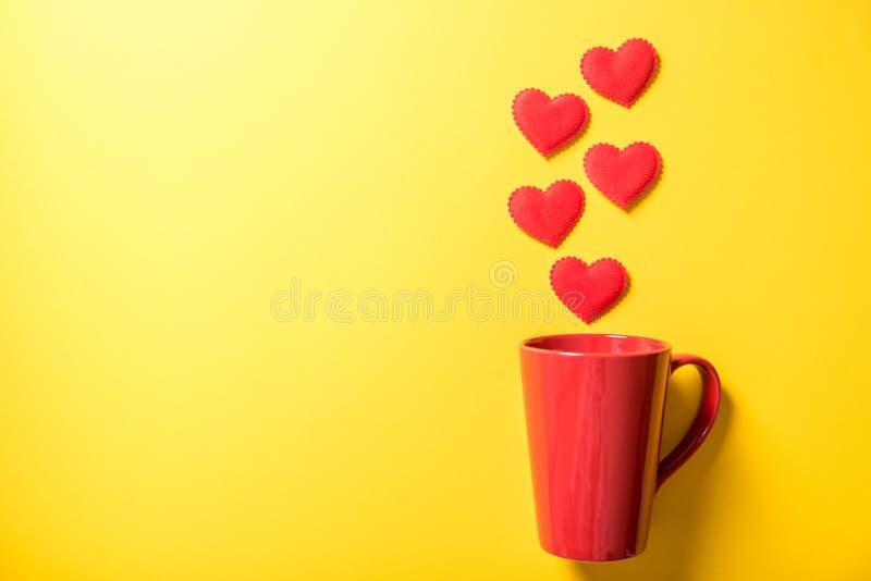 Taza de café roja con el corazón del humo en fondo de papel amarillo foto de archivo libre de regalías