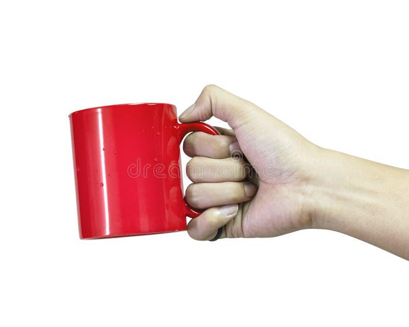 Taza de café roja de la tenencia de la mano aislada en el fondo blanco Plantilla del envase de cer?mica para la bebida Trayectori imagen de archivo libre de regalías
