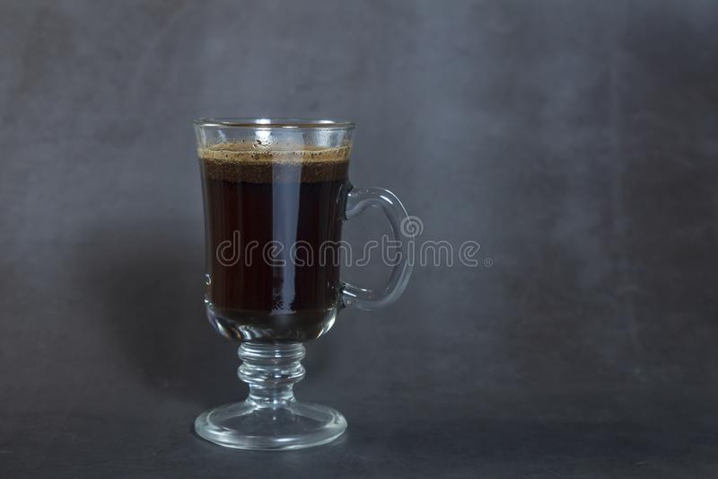 Taza de café sólo caliente en el vidrio alto foto de archivo
