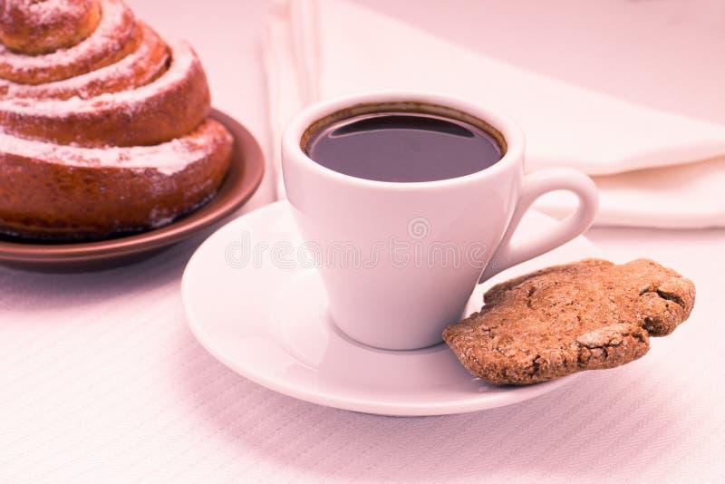 Taza de café sólo con un bollo y una galleta dulces imágenes de archivo libres de regalías