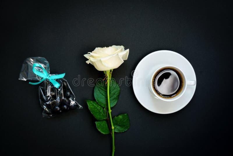 Taza de café sólo, de dulces del chocolate y de rosa blanca en el fondo negro, visión superior, espacio de la copia Imagen entona imagen de archivo libre de regalías