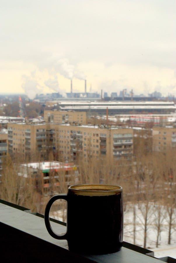 Taza de café sólo en el fondo de un panorama borroso del invierno de la ciudad y de los tubos que fuman de fábricas de productos  fotografía de archivo