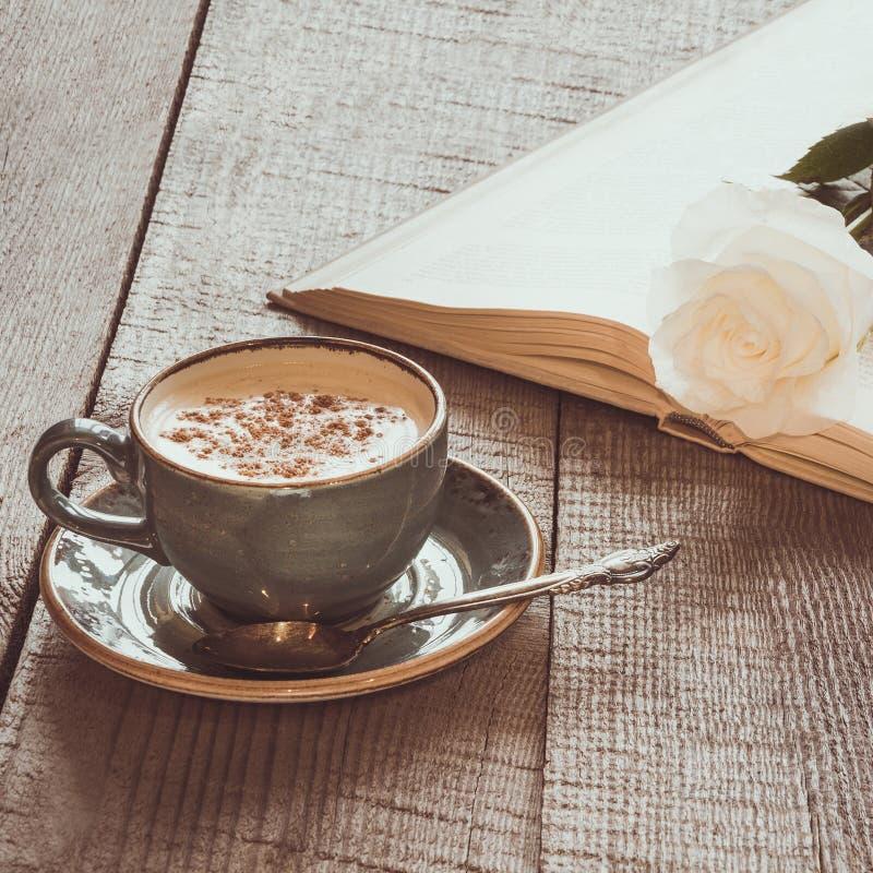 Taza de café sólo y de libro abierto con la rosa del blanco en el tablero de madera Vintage entonado Cierre para arriba fotografía de archivo