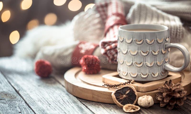 Taza de café sobre bokeh de las luces de la Navidad en hogar en la tabla de madera con el suéter en un fondo y decoraciones Decor imágenes de archivo libres de regalías