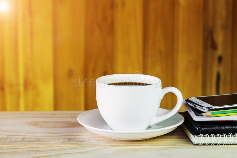 Taza de café, teléfono elegante y cuaderno en fondo de madera de la tabla fotografía de archivo libre de regalías