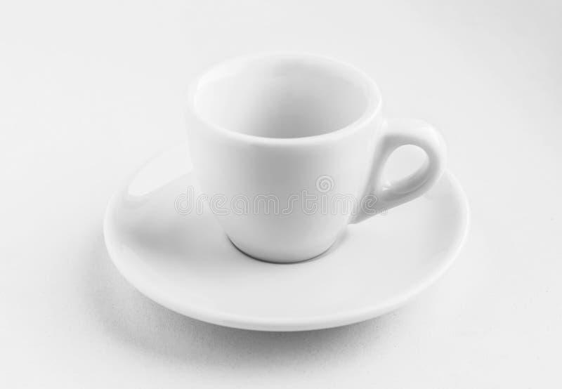 Taza de café vacía blanca con el platillo que se coloca en un fondo blanco, sombras claras que ponen en contraste de él, concepto imagen de archivo