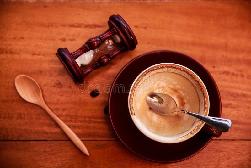 Taza de café vacía con el vidrio de la cuchara y de la arena en fondo de madera de la tabla de madera, fotos de archivo libres de regalías