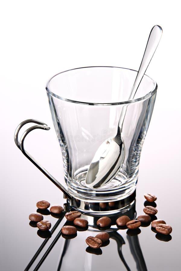 Taza de café vacía con los granos y la cuchara de café imagen de archivo