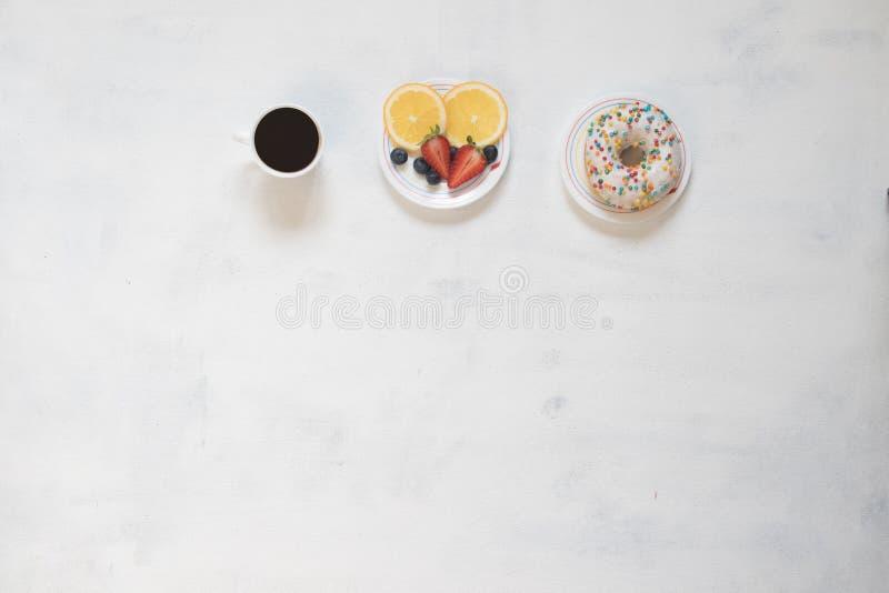 Taza de café y de buñuelo con la crema de la cuajada adornada con las migas de la fruta roja en el fondo blanco foto de archivo libre de regalías