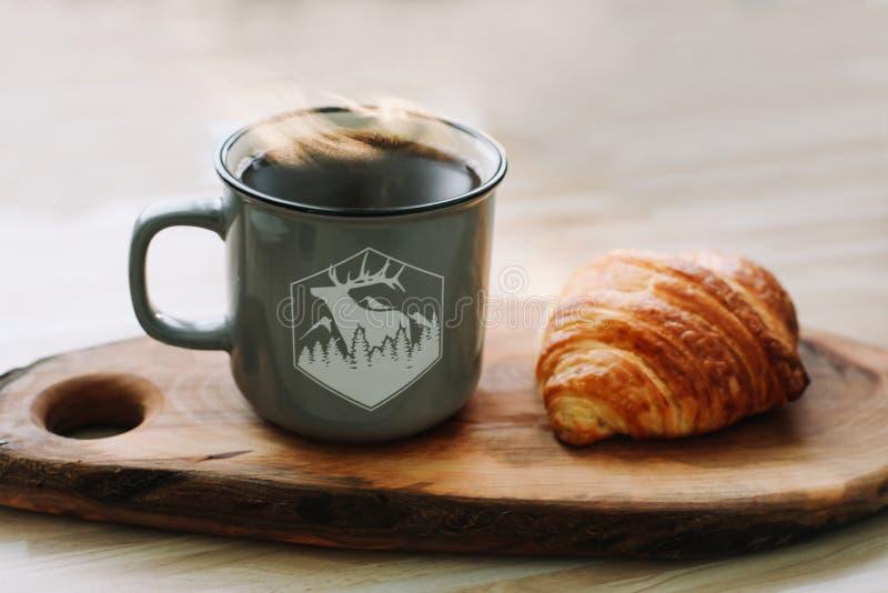 Taza de café y de cruasán calientes en una bandeja de madera Concepto del desayuno fotografía de archivo libre de regalías