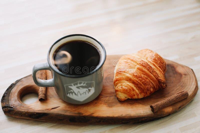 Taza de café y de cruasán calientes en una bandeja de madera Concepto del desayuno foto de archivo