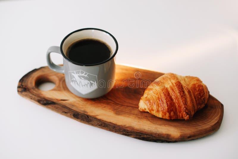 Taza de café y de cruasán calientes en una bandeja de madera Concepto del desayuno imagen de archivo