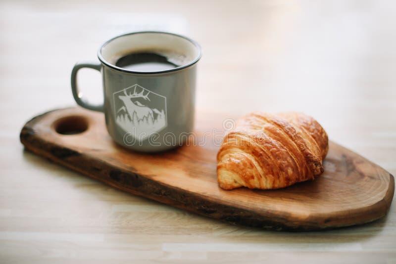Taza de café y de cruasán calientes en una bandeja de madera Concepto del desayuno imagen de archivo libre de regalías