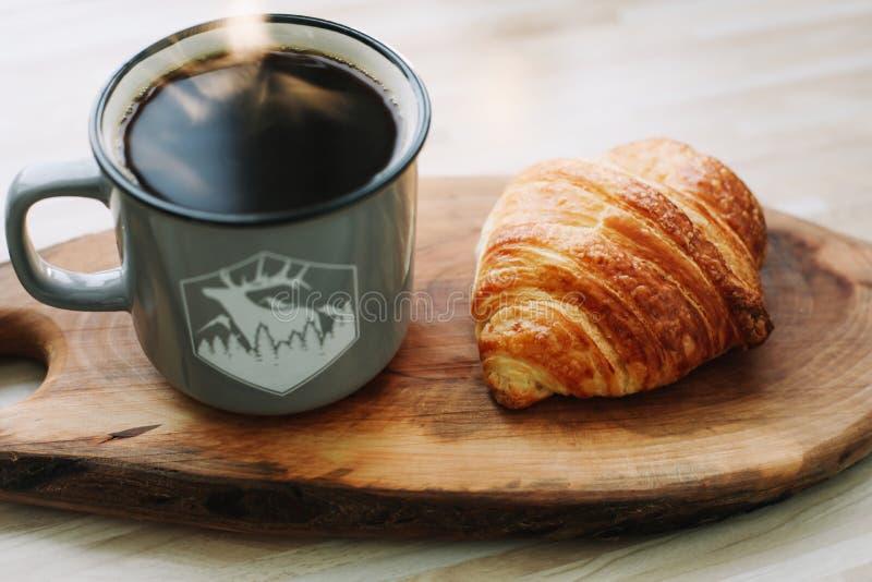 Taza de café y de cruasán calientes en una bandeja de madera Concepto del desayuno imágenes de archivo libres de regalías