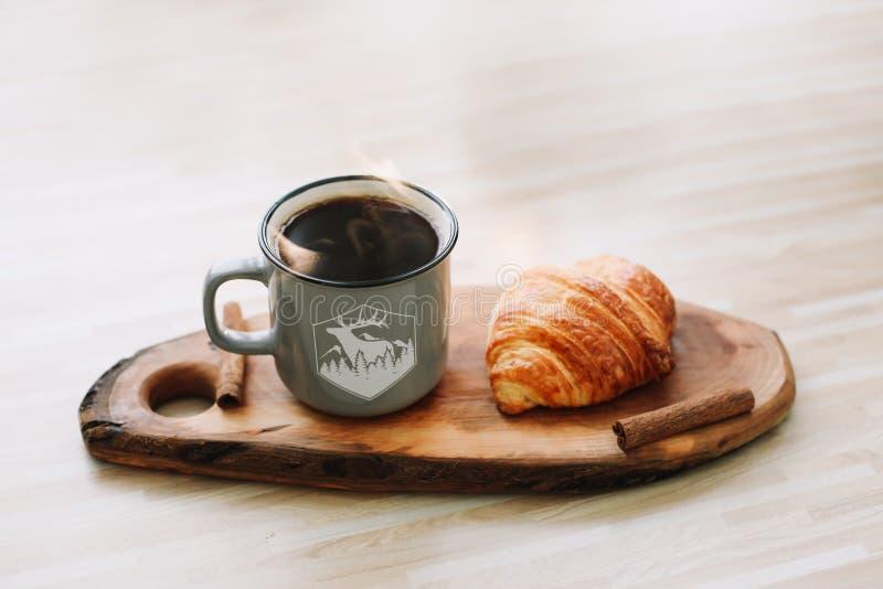 Taza de café y de cruasán calientes en una bandeja de madera Concepto del desayuno fotografía de archivo