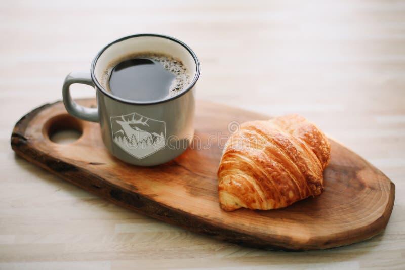 Taza de café y de cruasán calientes en una bandeja de madera Concepto del desayuno fotos de archivo libres de regalías