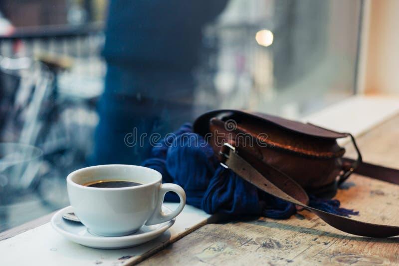 Taza de café y de bolso por la ventana fotos de archivo