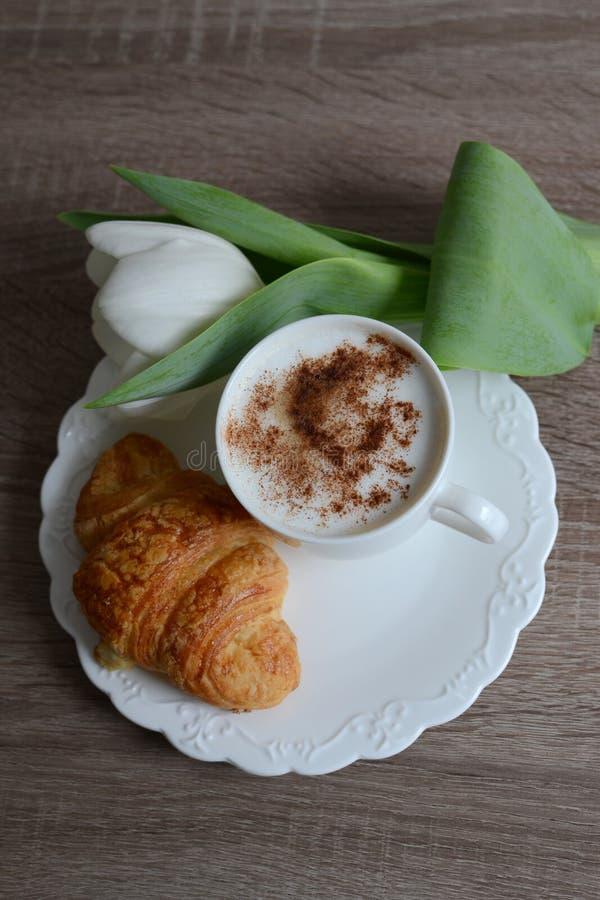 Taza de café y de cruasán delicioso imagenes de archivo