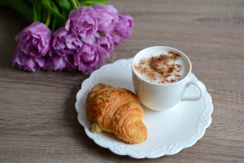 Taza de café y de cruasán delicioso imagen de archivo