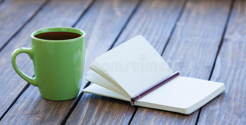 Taza de café y de cuaderno con el lápiz imagenes de archivo