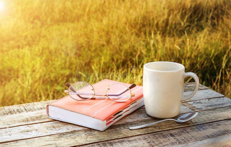 Taza de café y de cuaderno en la tabla de madera foto de archivo