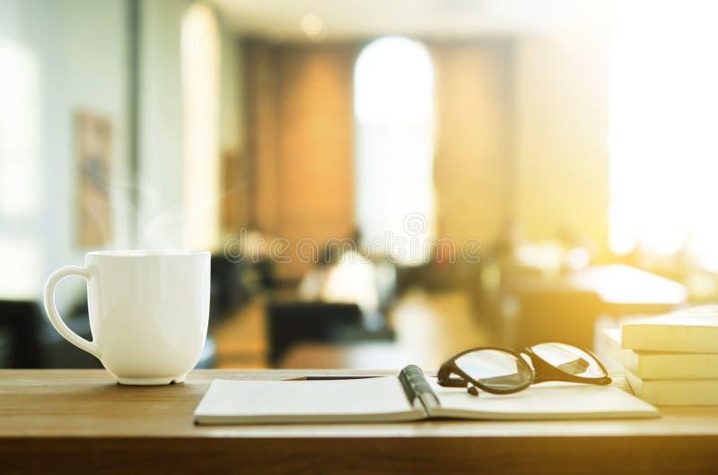 Taza de café y de cuaderno en la tabla de madera Descanso para tomar café en el MOR imagen de archivo