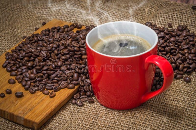 Taza de café y de granos de café derramados fotos de archivo