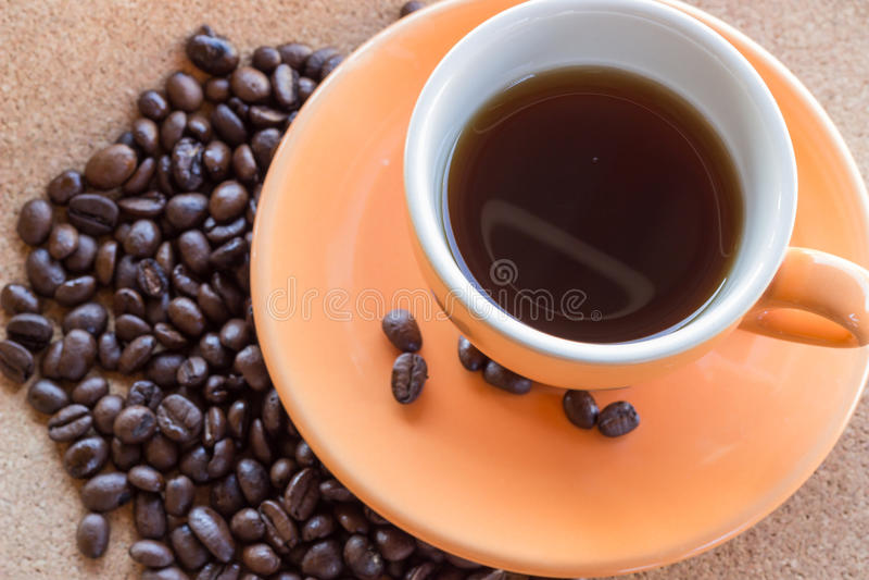 Taza de café y de granos de café en el papel marrón de la tela foto de archivo
